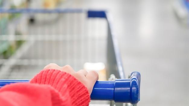 Cliente feminino com carrinho turva movimento de loja de departamento de supermercado