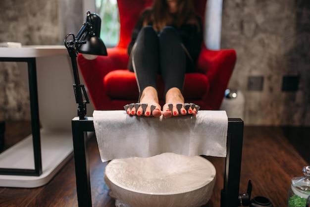 Cliente feminino em procedimento cosmético de pedicure em salão de beleza.