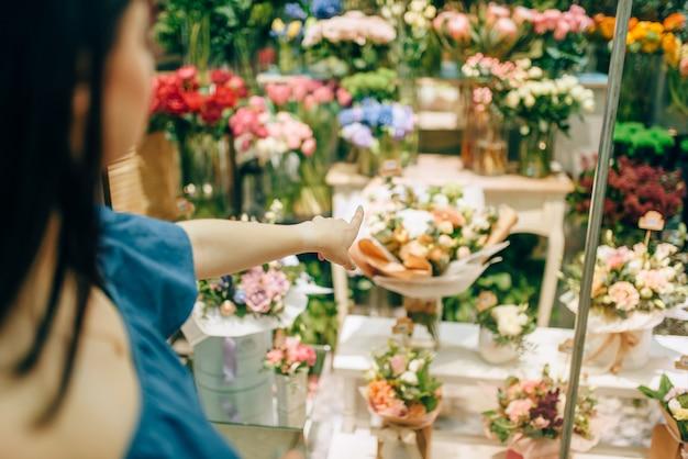 Cliente feminino escolhe flores para a preparação do buquê.