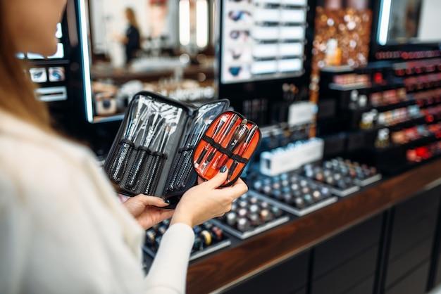 Cliente feminino escolhendo ferramentas de cosméticos na loja de maquiagem. escolha de verniz para unhas em loja de beleza, salão de maquiagem