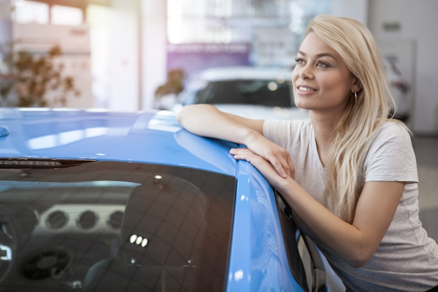 Cliente feminino feliz, apoiando-se em seu novo automóvel, sorrindo, olhando para longe sonhadora