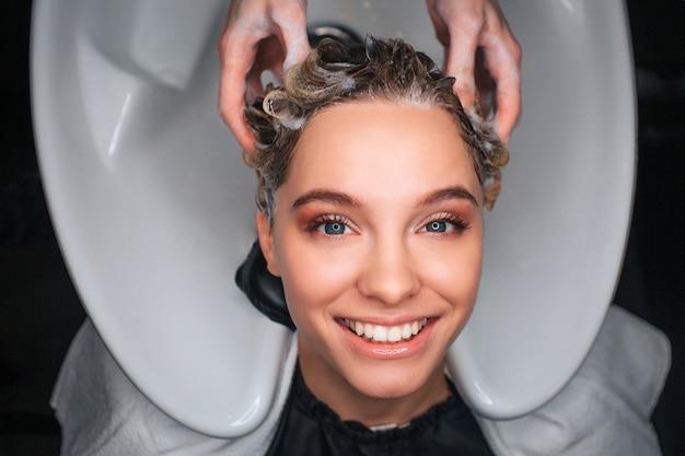 Cliente feminino feliz sorrindo enquanto cabeleireiro massageando o cabelo