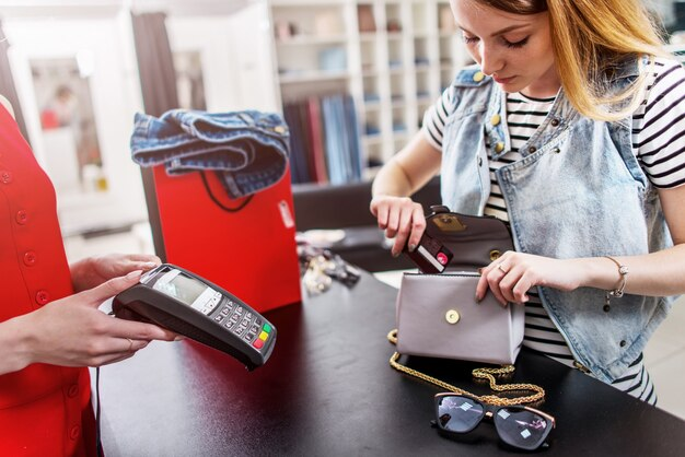 Cliente feminino jovem, em pé na mesa de dinheiro, pagando com cartão de crédito