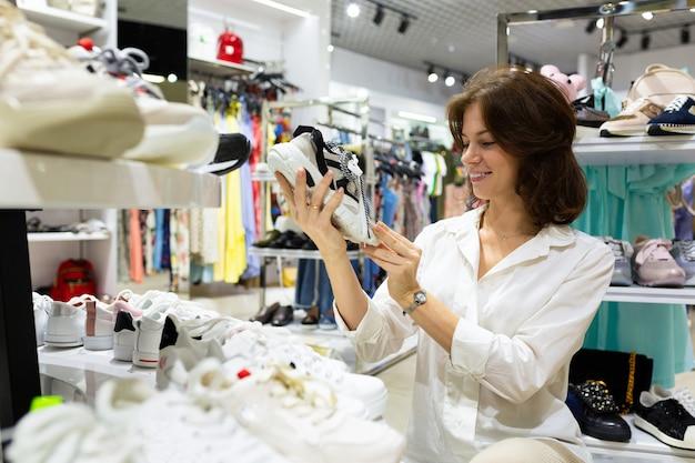 Cliente feminino jovem, segurando o par de sapatos da moda no departamento de sapatos