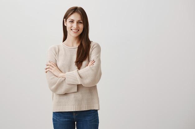 Cliente feminino satisfeito e confiante sorrindo com os braços cruzados satisfeito