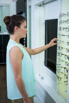 Cliente feminino selecionando óculos
