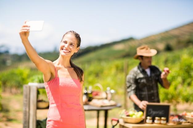 Cliente feminino tomando uma selfie na frente da banca de vegetais