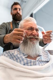 Cliente idoso fazendo cara no cabeleireiro