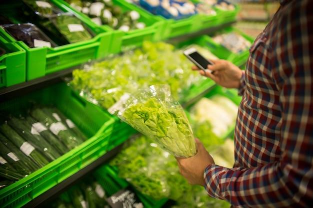 Cliente irreconhecível comprando ervas no supermercado