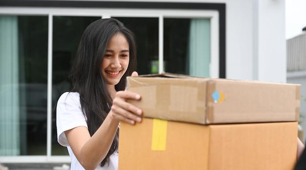 Cliente jovem mulher asiática recebendo pacote do entregador em casa.
