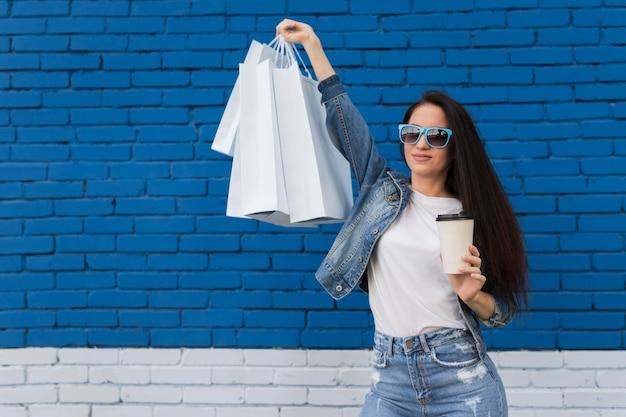 Cliente jovem segurando sacolas de compras e café