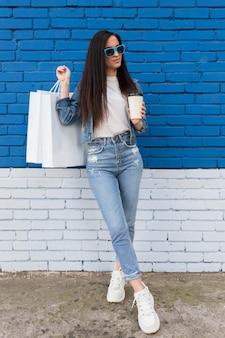 Cliente jovem segurando uma visão geral de sacolas de compras