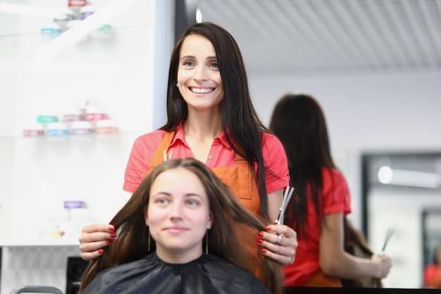 Cliente jovem sentado na cadeira em frente ao cabeleireiro no salão de beleza. cortes de cabelo de mulheres elegantes e conceito de penteados