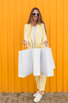 Cliente jovem vestindo roupas amarelas com bolsas brancas