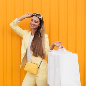 Cliente jovem vestindo roupas amarelas e segurando óculos de sol