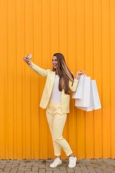 Cliente jovem vestindo roupas amarelas e tirando uma selfie