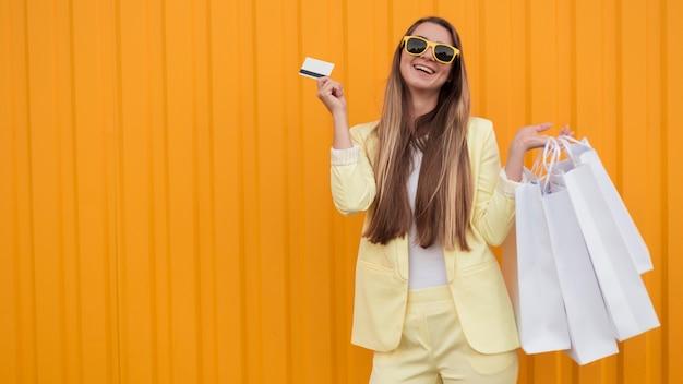 Cliente jovem vestindo roupas amarelas segurando um cartão de compras
