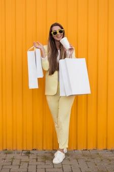 Cliente jovem vestindo roupas amarelas segurando voucher e bolsas