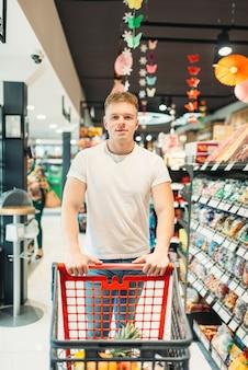 Cliente masculino com carrinho na loja de alimentos. homem comprando na mercearia, comprador no mercado