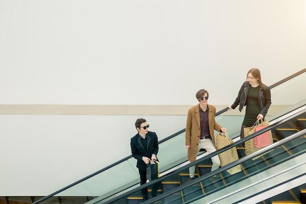 Cliente masculino e feminino na escada rolante no shopping