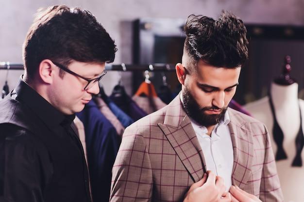 Cliente masculino no shopping tentando roupas de negócios, ajudado pelo assistente de loja