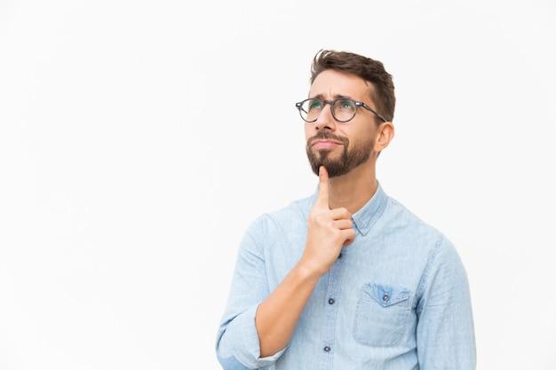 Cliente masculino pensativo positivo que estuda a oferta especial