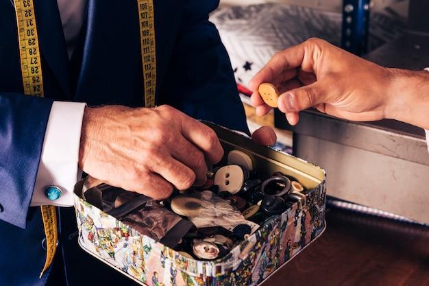 Cliente masculino, selecionando o botão do recipiente segurar pelo designer de moda