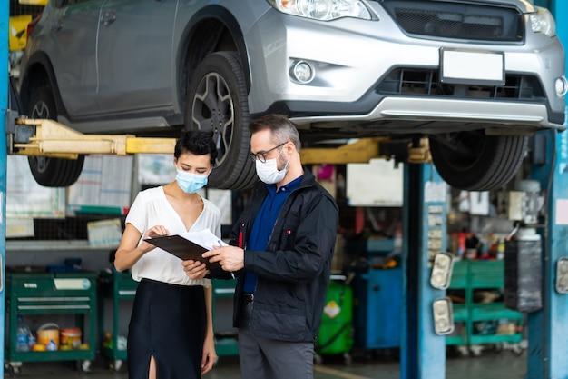 Cliente mecânico homem e mulher usando coronavírus de proteção de máscara facial médica e verificar a condição do carro antes do parto.
