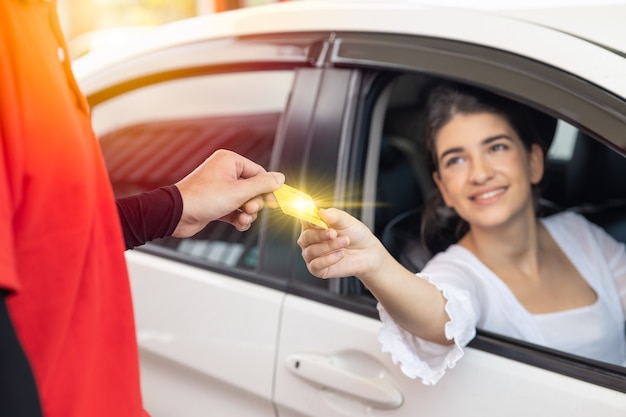 Cliente motorista de mulher feliz dando pagamento em dinheiro de cartão de crédito para a equipe pelo custo do combustível no posto de gasolina ou taxa de serviço na garagem