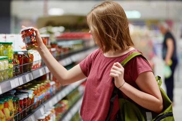 Cliente muito jovem femake mantém enlatados em recipiente de vidro, fica na loja de alimentos, vestido com roupas casuais