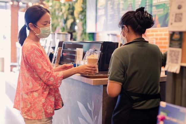 Cliente mulher asiática com máscara protetora recebe bebida do garçom no balcão do café