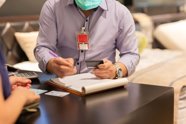 Cliente mulher com máscara protetora, pagamento com cartão de crédito.