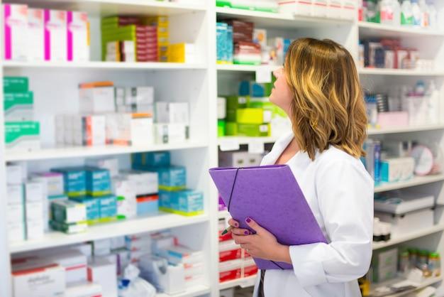 Cliente mulher, com, um, pasta, em, a, farmácia, olhar, a, medicamentos, prateleira