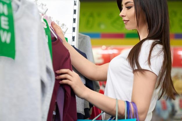 Cliente no shopping escolhendo blusa.