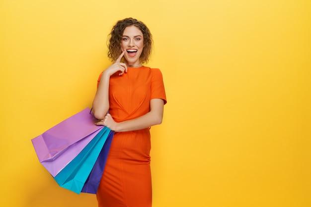 Cliente novo encantador que está com sacos de papel coloridos