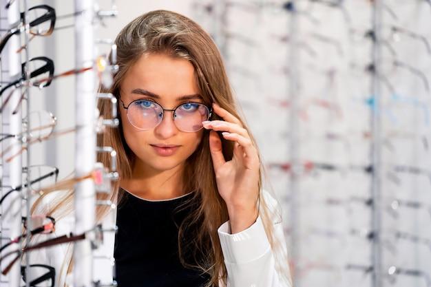 Cliente ou oculista do sexo feminino em pé com uma quantidade de óculos na loja de ótica