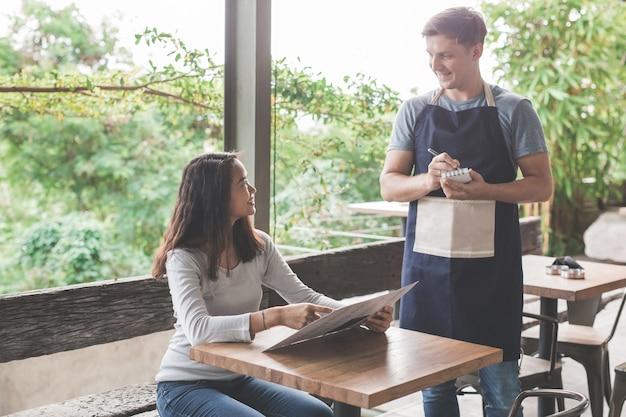 Cliente pedindo comida para a garçonete no café