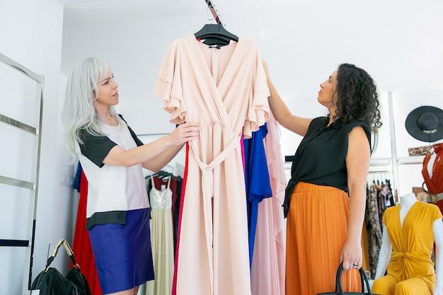 Cliente pensativo e vendedora examinando vestidos juntos na prateleira, escolhendo roupas em loja de moda. vista lateral. conceito de compras ou varejo