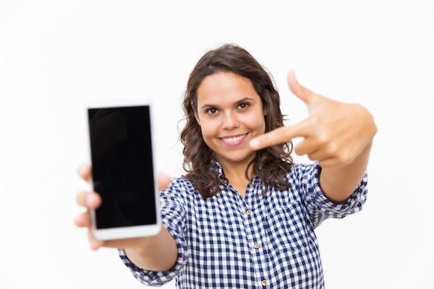 Cliente positivo feliz, apontando o dedo na tela do telefone em branco