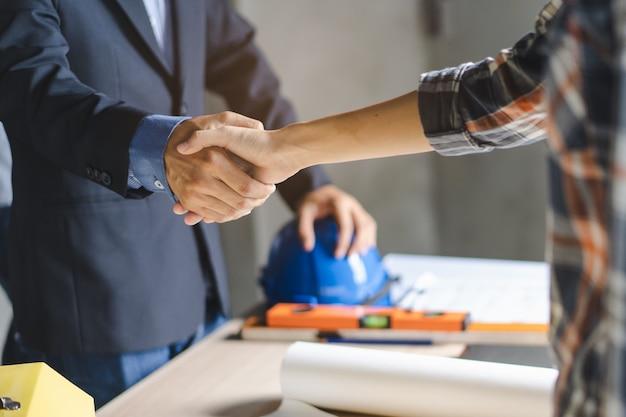 Cliente que agita as mãos com o construtor da equipe no local de renovação.