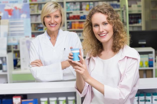 Cliente que mostra o frasco de medicamentos