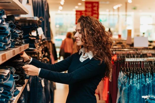 Cliente que olha a roupa dentro na loja.
