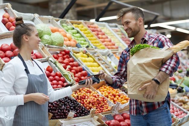 Cliente que paga pelo smartphone no supermercado