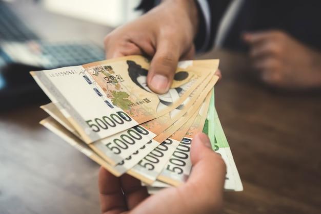 Cliente que recebe dinheiro, moeda da coreia do sul ganhou, de um empresário
