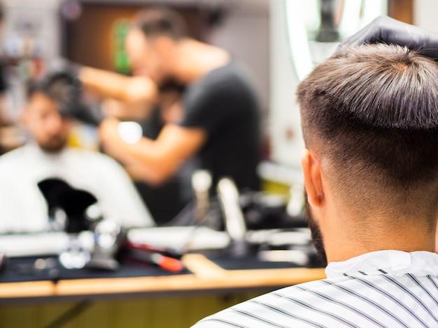 Cliente recebendo um novo corte de cabelo por trás