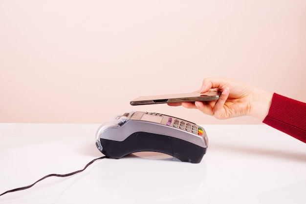Cliente segurando o telefone perto do terminal nfc faz pagamento móvel sem contato usando o conceito de aplicativo na loja