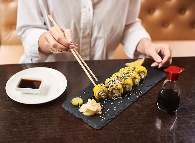 Cliente segurando palitos de comida e comendo uma refeição asiática no almoço.