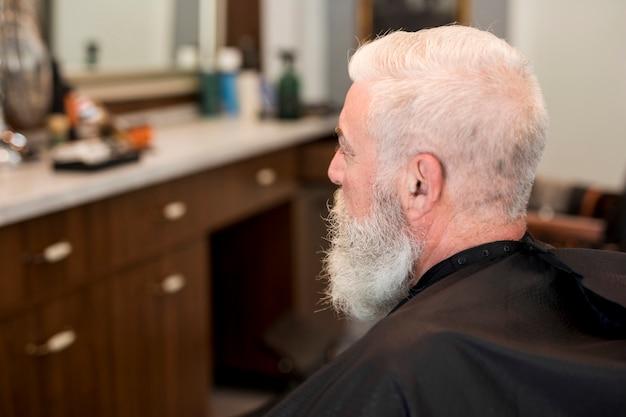Cliente sênior com capa na barbearia