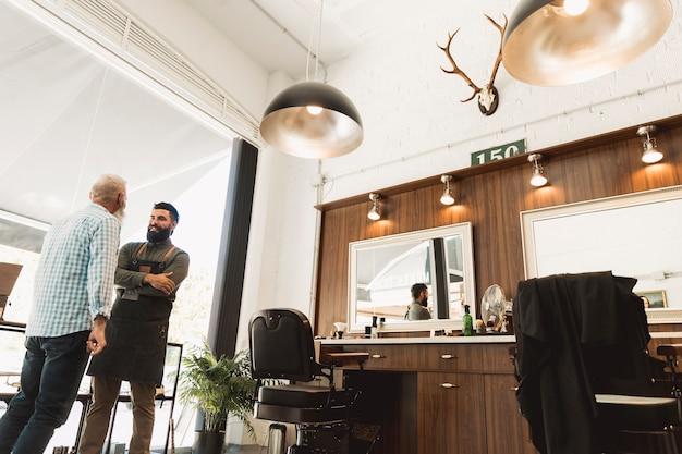 Cliente sênior e cabeleireiro discutindo sobre o trabalho