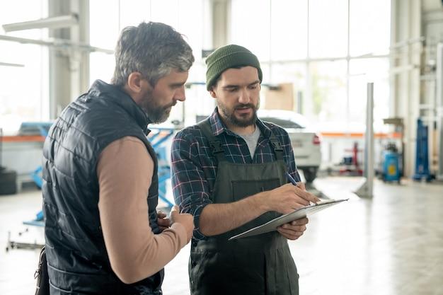 Cliente sério do sexo masculino, barbudo, de serviço de automóveis contemporâneos, olhando documento na posse de um jovem reparador, explicando-lhe os termos do acordo